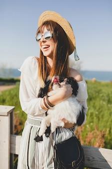 Mulher elegante jovem feliz no campo, segurando um cachorro, humor positivo e feliz, verão, chapéu de palha, roupa de estilo boêmio, óculos de sol, sorrindo