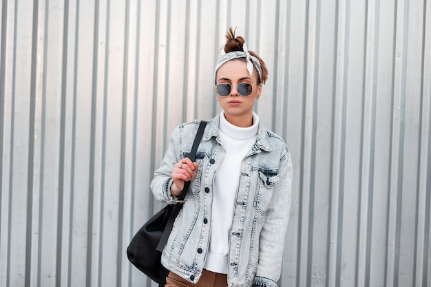 Mulher elegante jovem hippie em óculos de sol na bandana da moda em jaquetas jeans de verão com uma camisola de malha com uma mochila de couro preto em um dia quente de verão fica perto de uma parede de metal brilhante. garota legal.