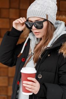 Mulher elegante jovem hippie no chapéu de malha com um moletom azul com uma jaqueta de inverno em óculos de sol em pé perto da parede de madeira e segurando uma xícara vermelha de café quente e saboroso. menina na moda.