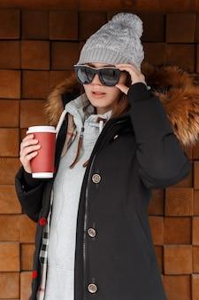 Mulher elegante jovem hippie no chapéu de malha de inverno em óculos de sol em uma jaqueta quente com um capuz de pele em uma camisola elegante posa perto de uma parede de madeira ao ar livre. linda garota bebe café quente.