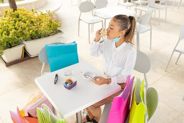 Mulher elegante jovem moderna bebendo café ao ar livre na mesa do bar com sacolas coloridas usando smartphone, verificando o melhor preço online. nova viciada em compras, normal e sozinha, em um café-restaurante com máscara