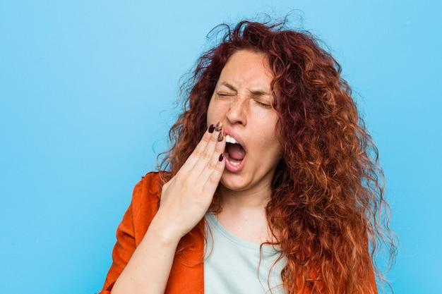 Mulher elegante jovem ruiva bocejando mostrando um gesto cansado, cobrindo a boca com a mão.