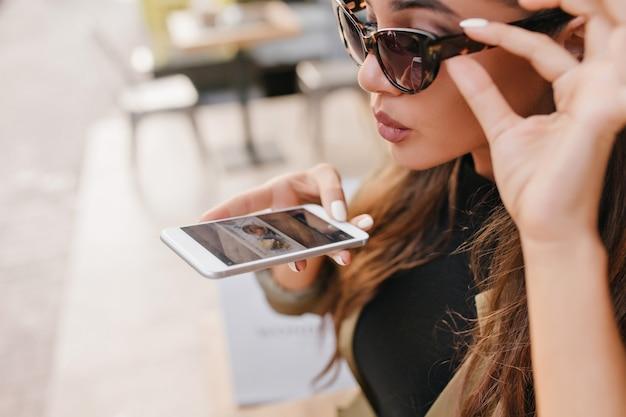 Mulher elegante, levemente bronzeada, segurando um smartphone na rua