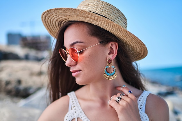 Mulher elegante lindo verão brilhante usando um chapéu de palha, brincos grandes e óculos de sol vermelhos