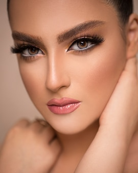 Mulher elegante maquiagem bronzeada promovendo cuidados com a pele