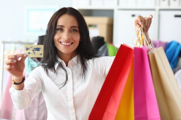 Mulher elegante mostra cartão de crédito e pacotes