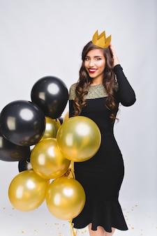 Mulher elegante muito alegre em vestido de noite preto de luxo e coroa amarela na cabeça, sorrindo e segurando balões amarelos e pretos.