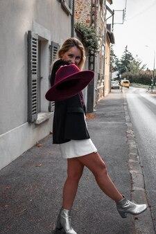 Mulher elegante na rua segurando um chapéu