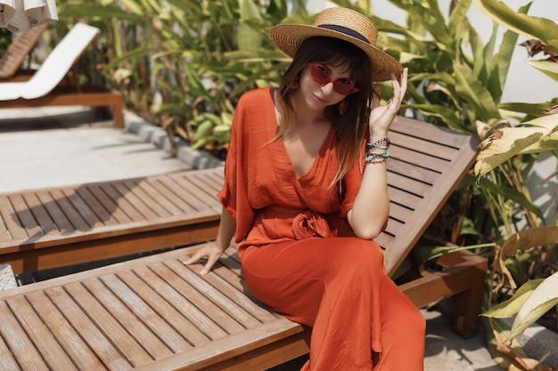 Mulher elegante no chapéu de palha e macacão laranja descansando em sua casa durante as férias em bali.