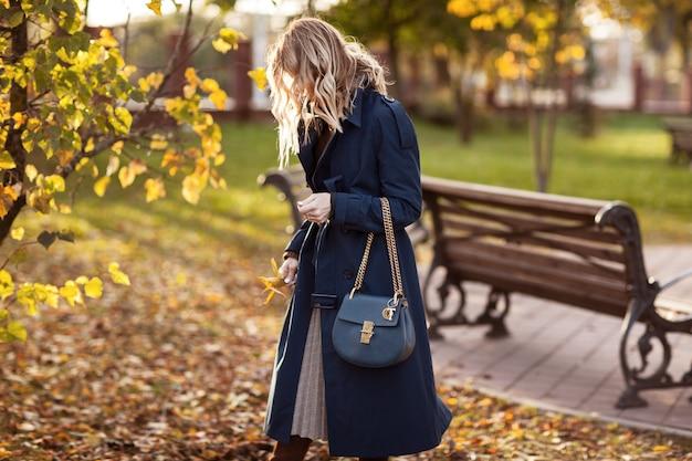 Mulher elegante passeios no parque outono.