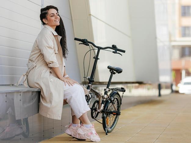 Mulher elegante posando com bicicleta