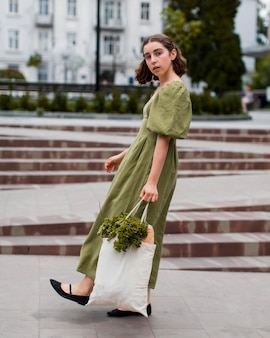 Mulher elegante posando com uma sacola de compras