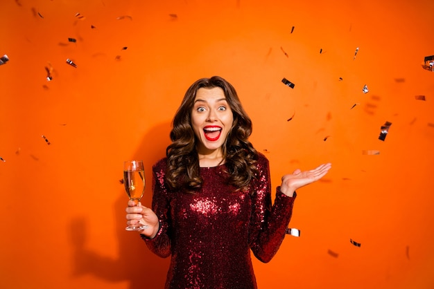 Mulher elegante posando contra a parede laranja