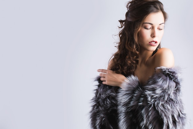 Mulher elegante posando em peles. luxo, estilo de vida rico.