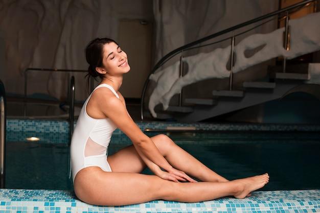 Mulher elegante posando junto à piscina no spa