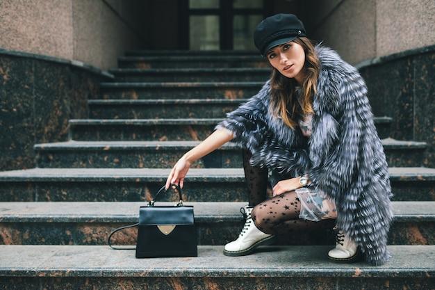 Mulher elegante posando na cidade com um casaco de pele quente, inverno, clima frio, usando boné preto, vestido, botas brancas, segurando uma bolsa de couro, tendência da moda de rua