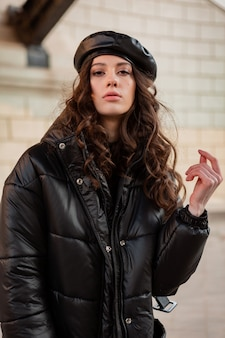 Mulher elegante posando no inverno outono tendência da moda casaco baiacu preto e boina com chapéu de couro na antiga e bonita rua usando sapatos de salto alto