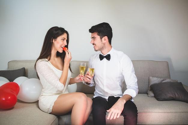 Mulher elegante que come uma morango ao brindar com o namorado