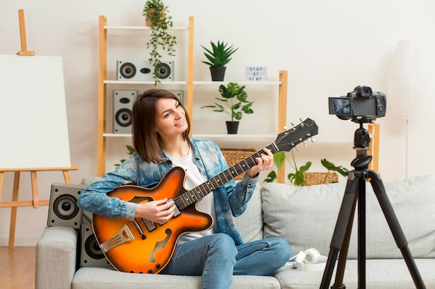 Mulher elegante, recodificando-se enquanto toca guitarra