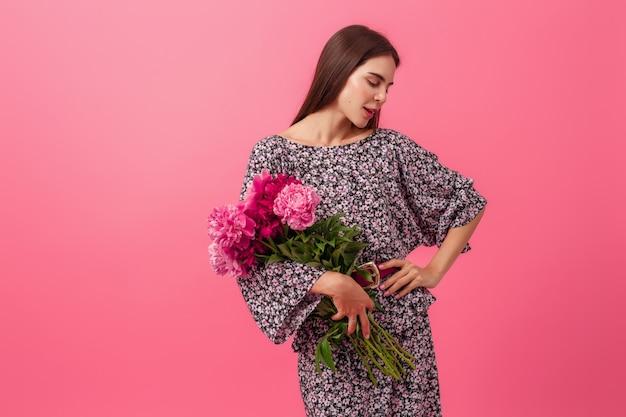 Mulher elegante rosa com vestido da moda de verão posando com buquê de flores de peônia
