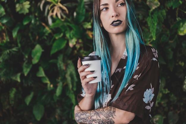 Mulher elegante, segurando o copo de café descartável