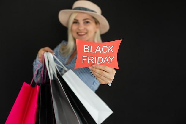 Mulher elegante segurando sacolas pretas, conceito de sexta-feira negra