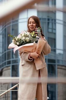 Mulher elegante segurando um buquê de flores do lado de fora e conversando ao telefone