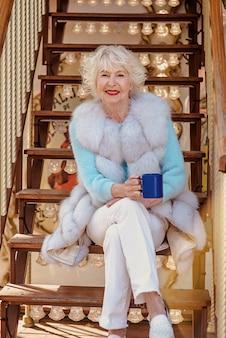 Mulher elegante sênior com casaco de pele e cabelos grisalhos sentada no carrossel bebendo chá e café
