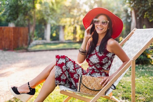 Mulher elegante sentada na espreguiçadeira falando no telefone inteligente com roupa de estilo tropical, tendência da moda de verão, top, saia, skinny, bolsa de palha, chapéu vermelho, óculos de sol, acessórios, sorrindo, férias