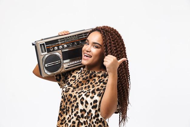 Mulher elegante, sorrindo e segurando uma caixa de som vintage com fita cassete no ombro, isolada contra uma parede branca