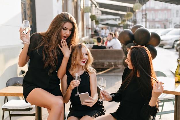 Mulher elegante surpresa cobrindo a boca com a mão, enquanto olha para a tela do telefone durante a festa