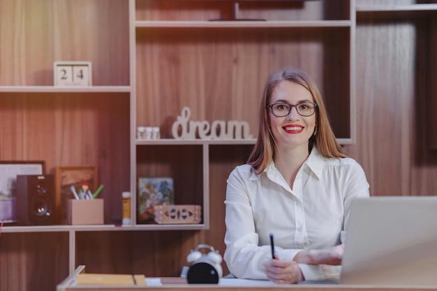 Mulher elegante trabalha em uma mesa de laptop em um escritório moderno
