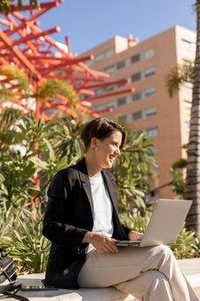 Mulher elegante trabalhando em um laptop do lado de fora