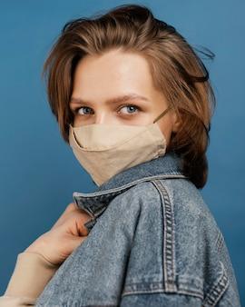 Mulher elegante usando jaqueta jeans e máscara