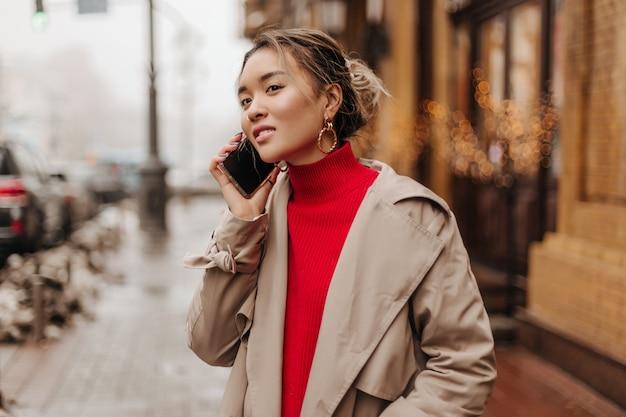 Mulher elegante usando sobretudo leve e suéter brilhante falando ao telefone com ótimo humor e caminhando pela cidade