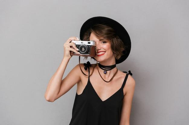 Mulher elegante usando vestido preto e chapéu fotografando na câmera retro, isolada sobre uma parede cinza
