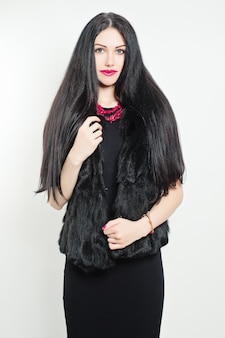 Mulher elegante usando vestido preto e jaqueta de pele