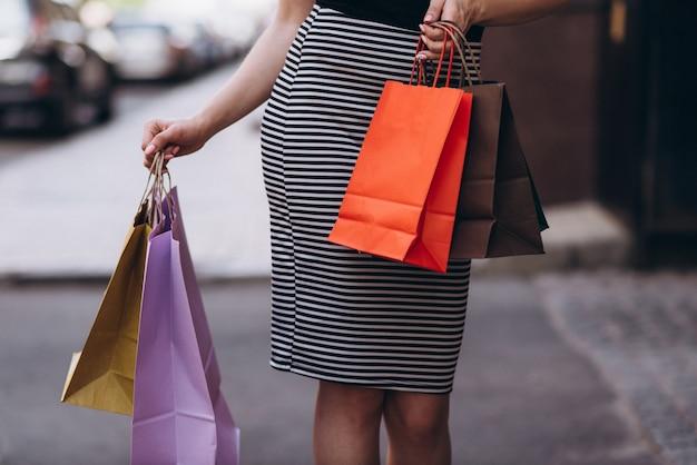 Mulher elegantemente vestida segura sacos de compras coloridos na rua, conceito de compras