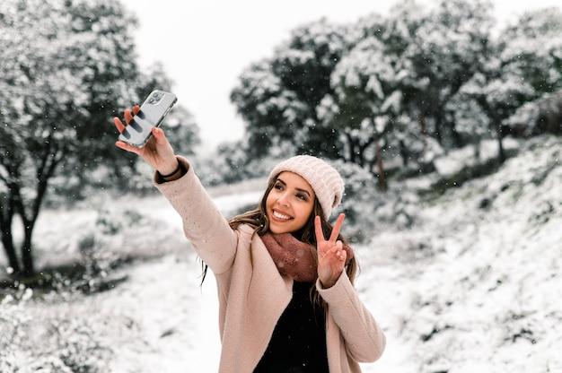 Mulher em agasalhos quentes em pé na floresta e tirando selfie da paisagem nevada cênica enquanto usa o smartphone