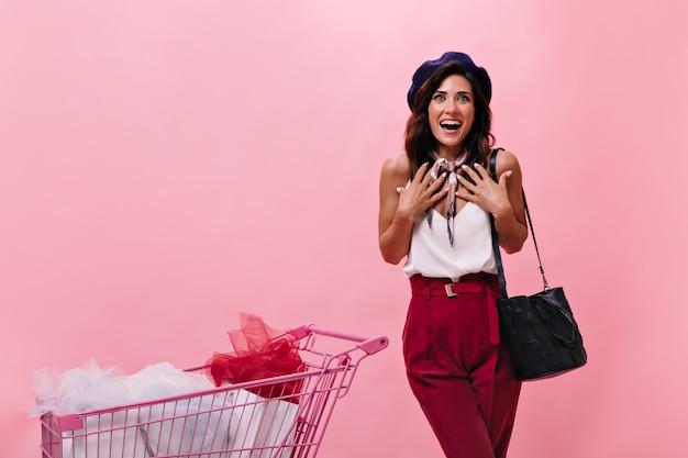 Mulher em alegre surpresa olha para a câmera e posa ao lado do carrinho rosa. senhora de blusa branca e calças brilhantes ri em fundo isolado.