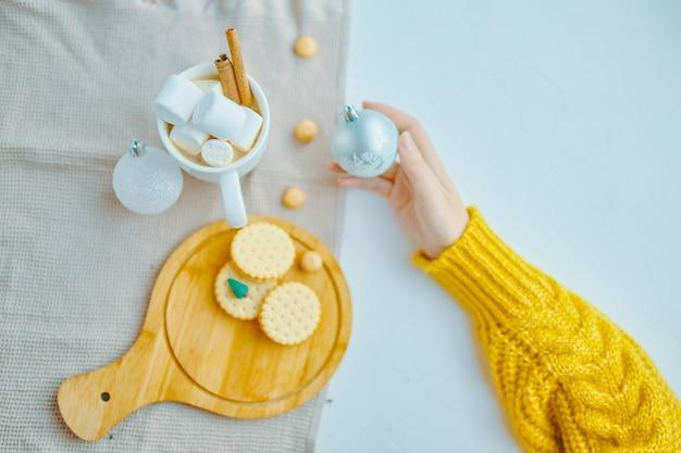 Mulher, em, amarela, suéter, segurando, bola natal, para, decoração, com, café, marshmallow