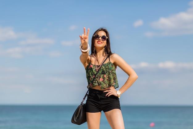Mulher em autfit tropical elegante, posando na praia.