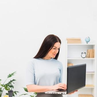 Mulher, em, azul, digitando, ligado, teclado laptop