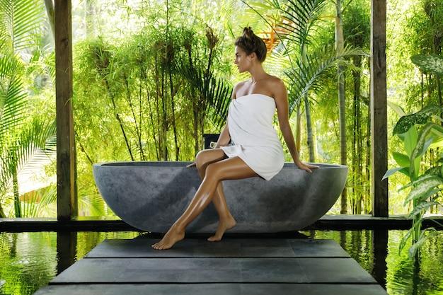 Mulher em banheiro ao ar livre com banheira de pedra em estilo balinês