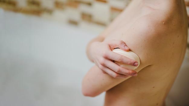Mulher em banho lavando com sabão