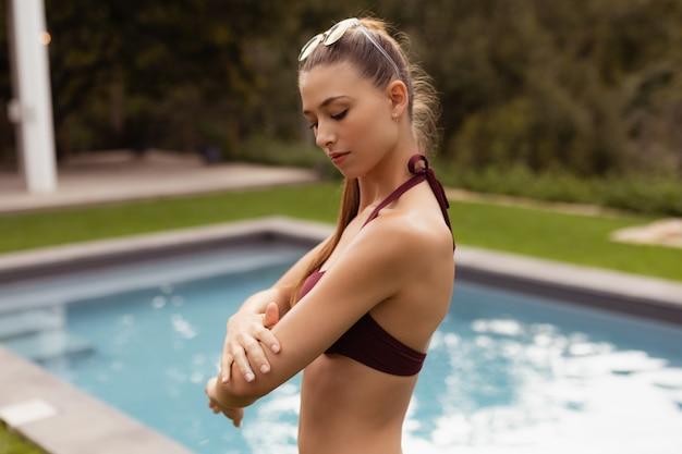 Mulher, em, biquíni, aplicando, protetor solar, loção, ligado, dela, corporal, perto, poolside