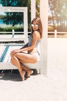 Mulher, em, biquíni, sentando, em, pavilhão praia
