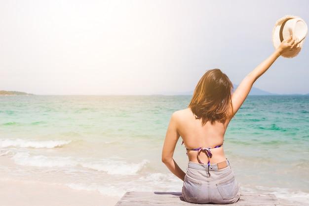 Mulher, em, biquíni, sentando praia, desfrutando, verão