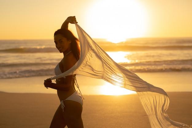 Mulher, em, biquíni, waving, echarpe, praia