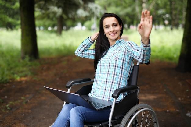 Mulher em cadeira de rodas acena com a mão em saudação